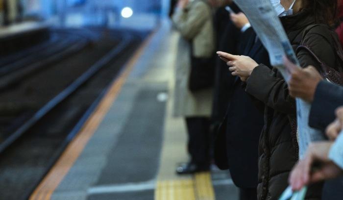 駅のホームでスマホを触る女性